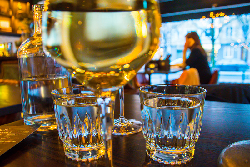 View from a table top through several beverage glasses, with restaurant customer sitting at distant table.