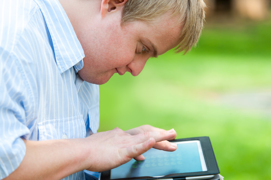 Boy with developmental disability holding a tablet and using touchscreen.