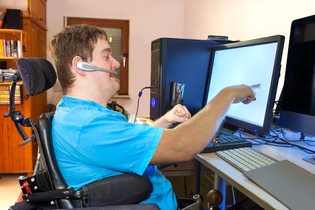 Young man in wheelchair using a computer touch screen while wearing a headset microphone.