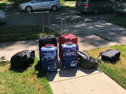 Several pieces of luggage sitting at a curb.