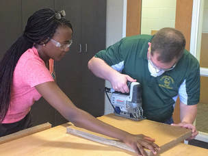 OT student and faculty using jigsaw to cut thick cardboard for a low-tech project.
